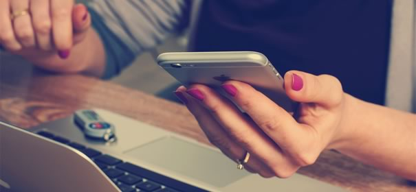 iPhoneを手に持つ女性の画像